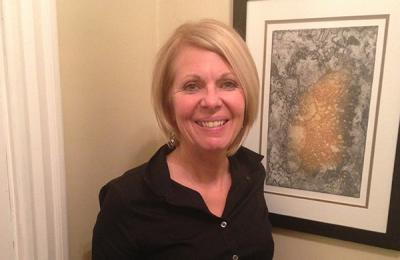 Headshot of Cheryl McLean standing by a beige wall beside a framed picture