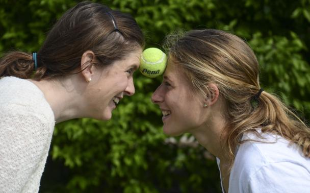 Two women balancing tennis ball between foreheads
