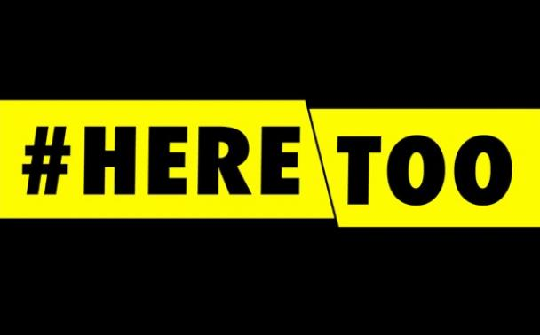 #HereToo words in yellow banner with black background